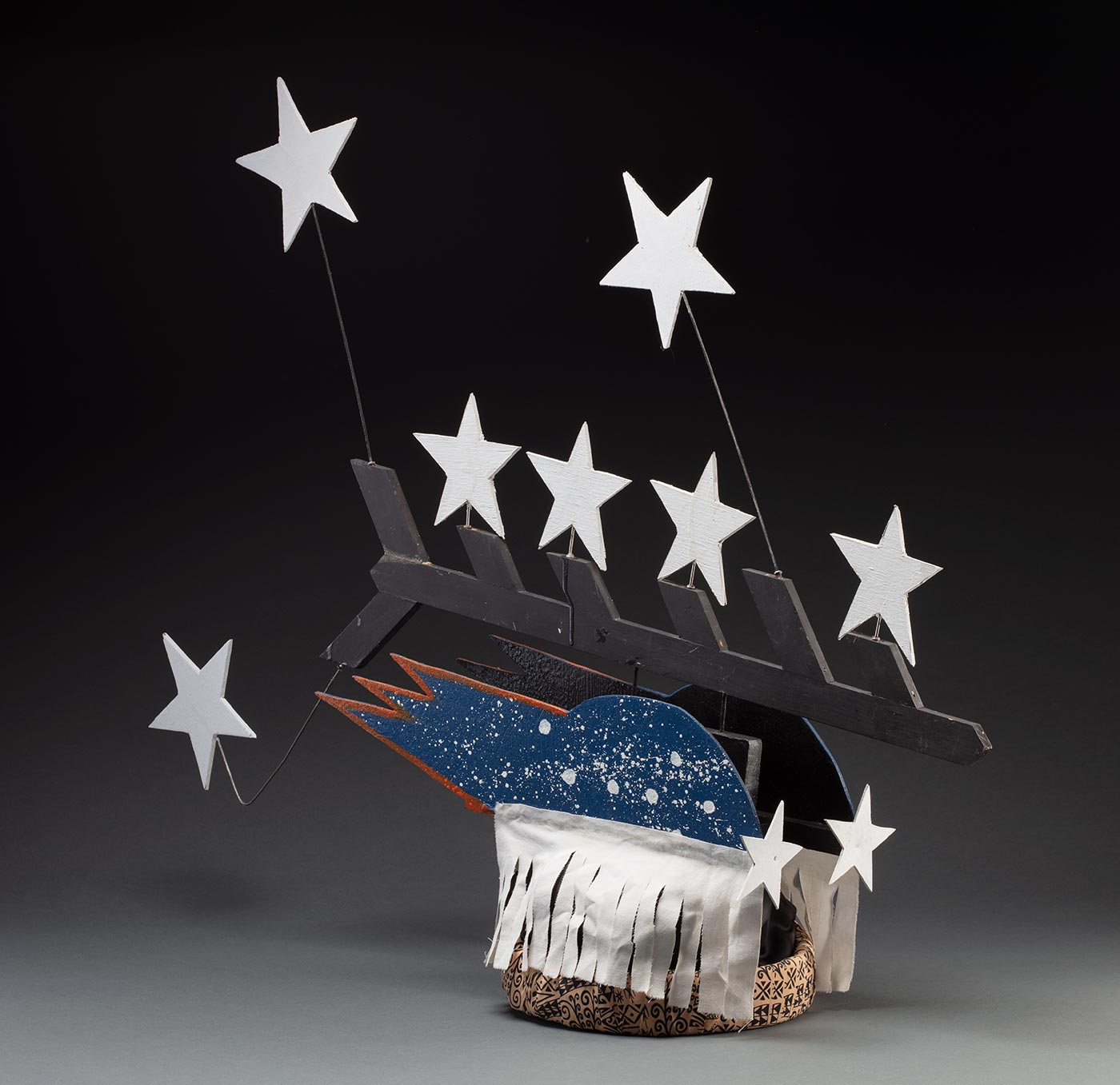 A headdress featuring seven stars protruding from a black painted piece of board forming half a fishbone pattern. It is connected to two pieces of board painted blue with white splatter and seven stars on each side with a white fabric fringe at the bottom. It is all attached to a fabric wrapped headband in the centre. - click to view larger image