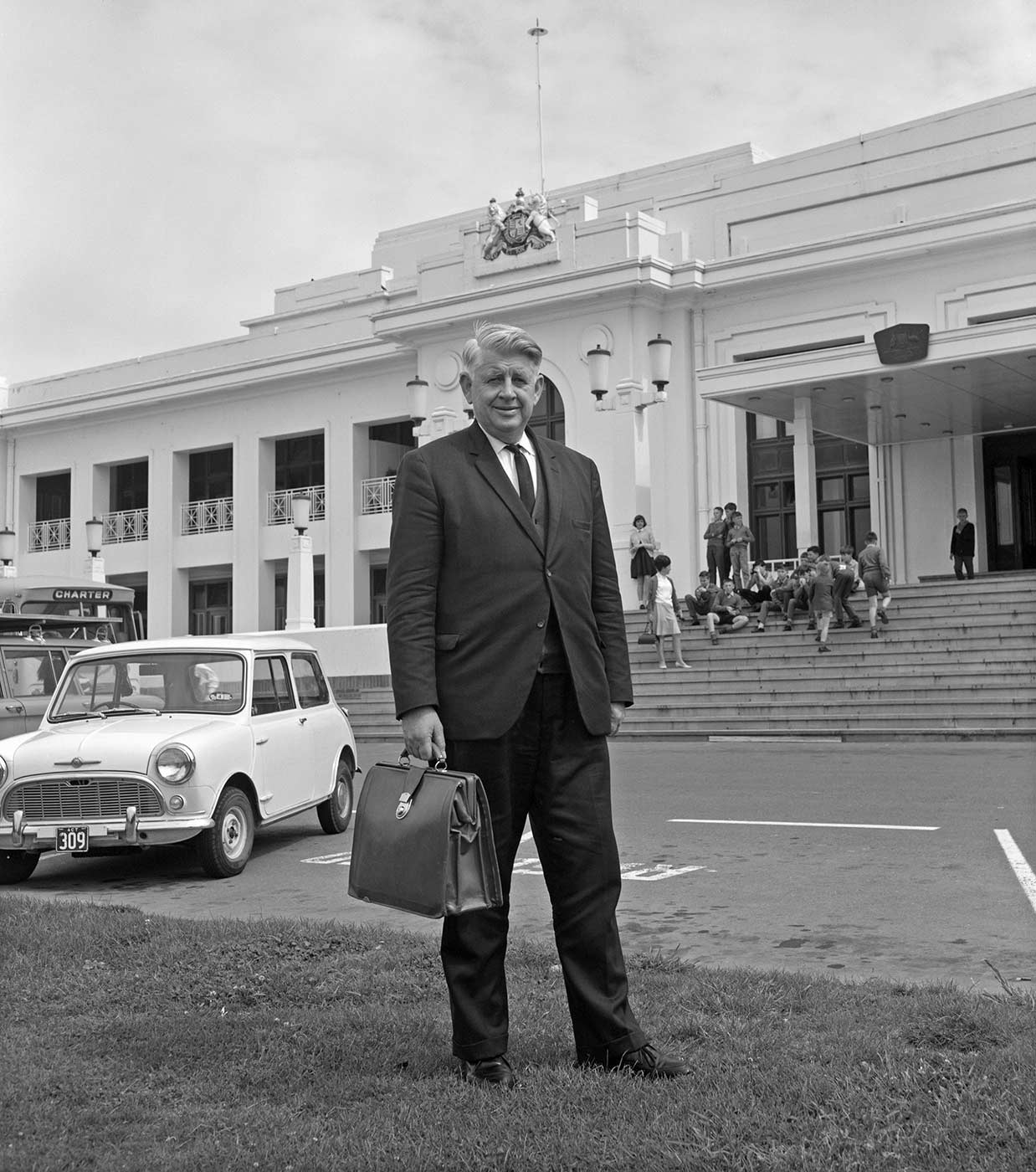 Black and white photo of a man in a business suit standing outside the front of parliament house in Canberra.