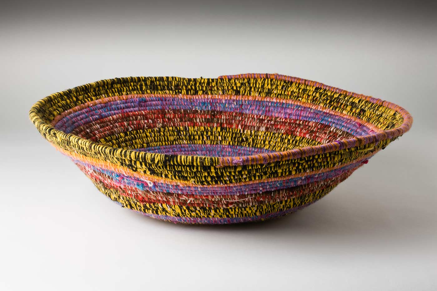 An oval coiled multicoloured yarn and plant fibre basket. The plant fibre in the centre of the basket is covered by yellow yarn, followed by horizontal alternate yarn coverings over the fibre. The yarn colours are purple, yellow, brown-white-pink, purple-yellow, pink-blue, red-brown-pink, purple-pink-blue, black-yellow, orange-pink. The top plant fibre is covered by half yellow-black and orange-purple yarn. - click to view larger image
