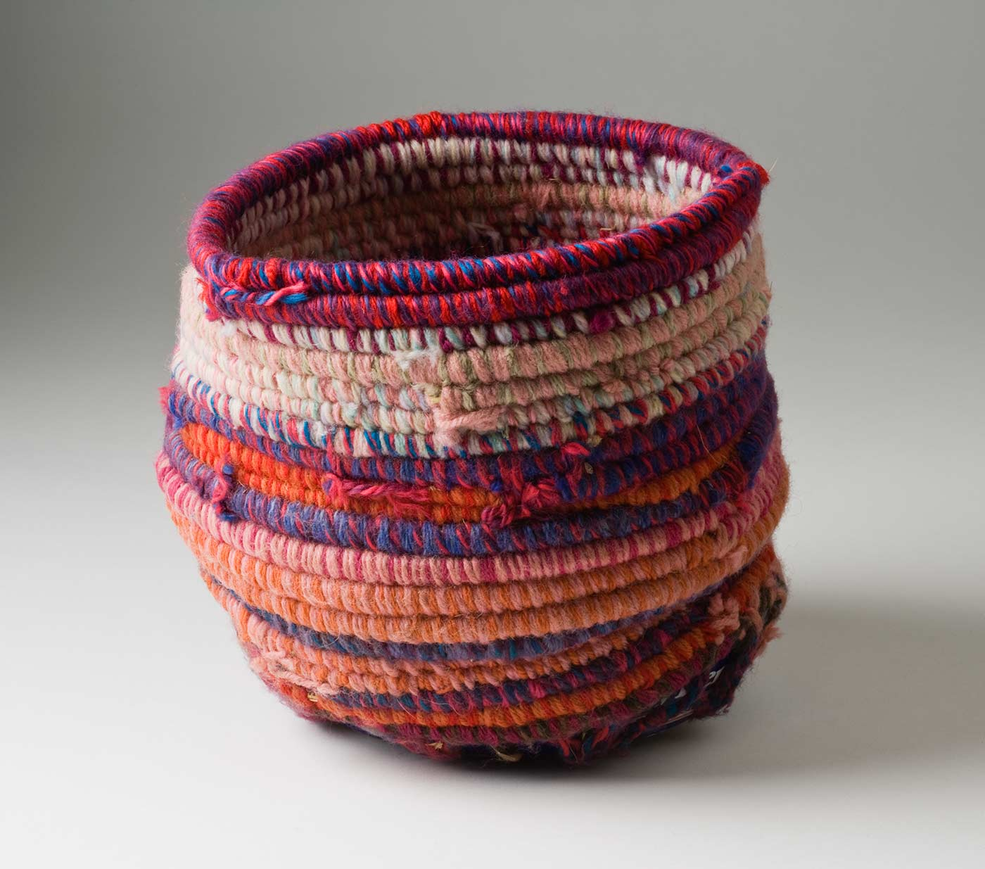 A cylindrical coiled multicoloured yarn and plant fibre basket with a metal base. The light and dark pink coiled yarn is mixed with colours of blue, orange, red and purple. The base of the basket is a blue and white coloured metal tin with burn marks to the bottom. Yarn is used to attach the base to the top section through holes that have been punched in the tin. - click to view larger image