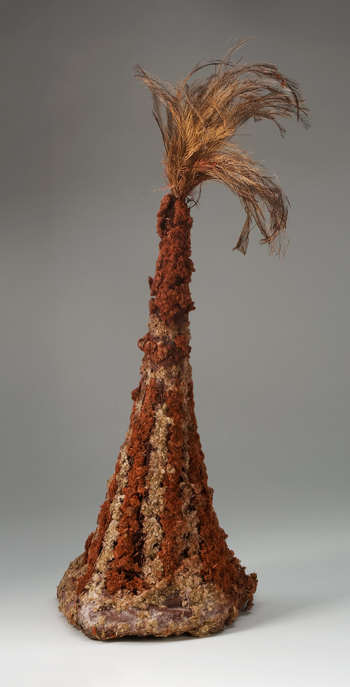 A tall conical headdress made of plant fibres attached to a firm circular ring at the base and covered with pigmented fluffy plant fibre with feathers at the top. The ring at the base is pigmented red and the plant fibre stalks are attached around it. The fibres are bunched together towards the top and wrapped with maroon coloured string. The plant stalks are covered with fluffy plant fibre which is decorated with red pigment in vertical stripes on the bottom half and red at the top. At the top of the headdress is a bunch of fluffy and spiky brown, tan and grey feathers. - click to view larger image