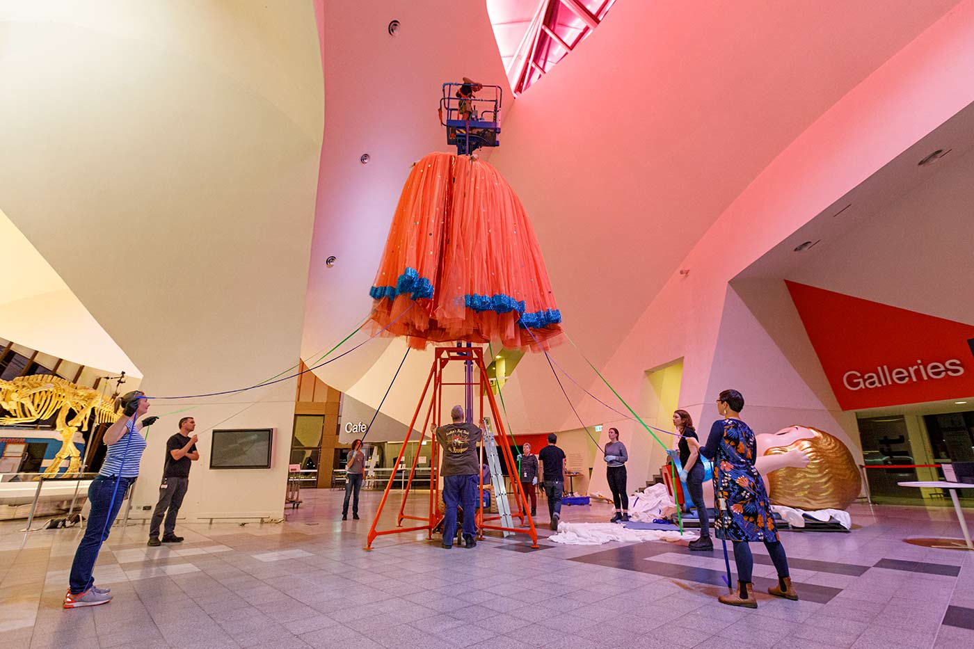 Colour photograph of staff installing a large peach skirt with blue trimming in a large hall. - click to view larger image