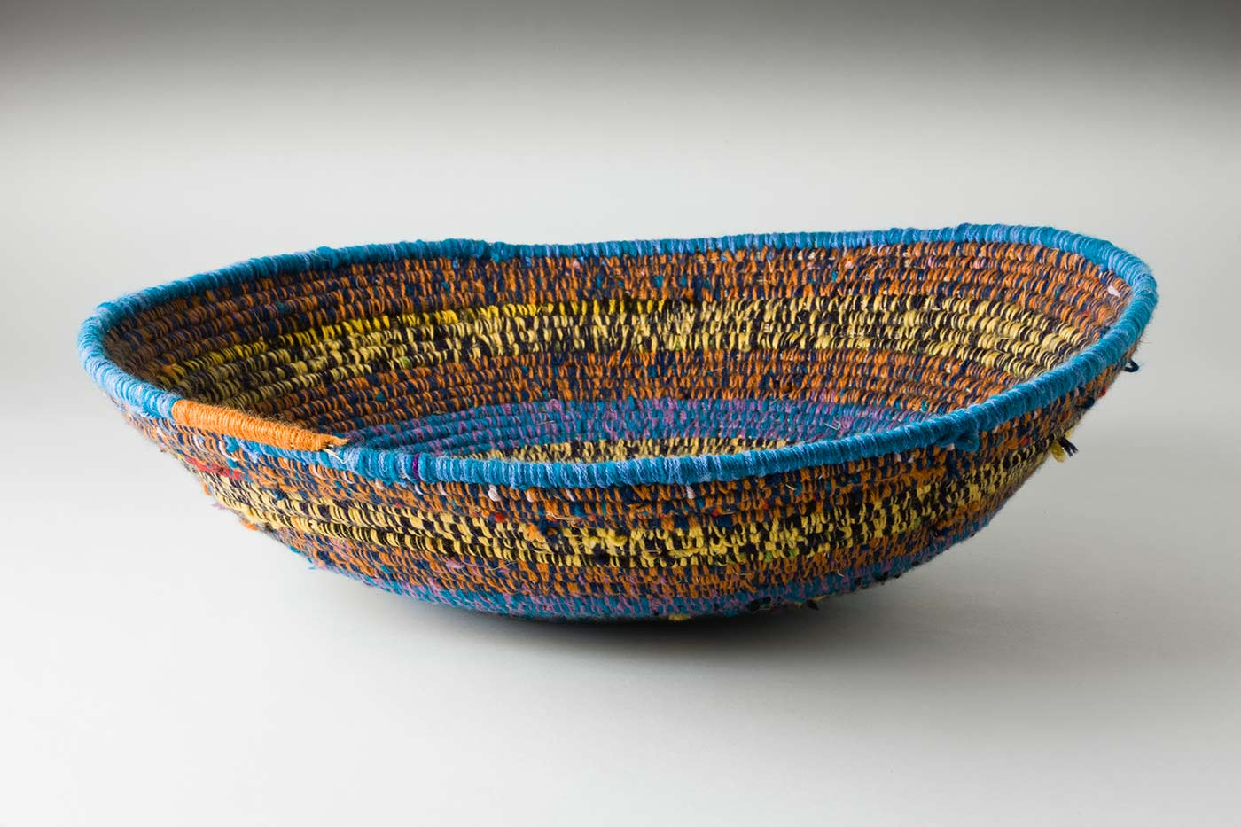 A circular coiled multicoloured yarn and plant fibre bowl shaped basket. The centre of the basket is pale pink yarn, covering the the plant fibre, followed by horizontal alternate yarn covering over the fibre. The yarn is coloured purple-green, green-grey, yellow-black, orange- blue. The top plant fibre is covered by green-blue yarn finished by an orange line. - click to view larger image