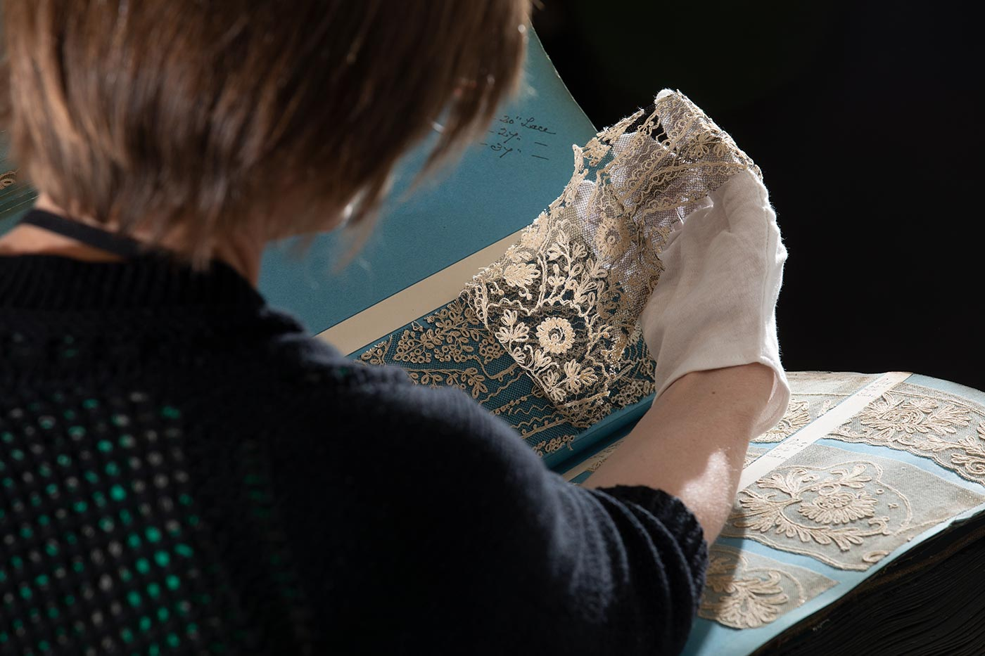 Colour photograph of a woman wearing conservation gloves and examining lace samples from a large sample book. - click to view larger image