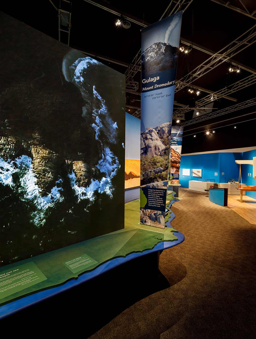 Interior view of a museum exhibition with a large image of a coastline in the foreground and a section featuring parts of a ship's interior in the distance. - click to view larger image