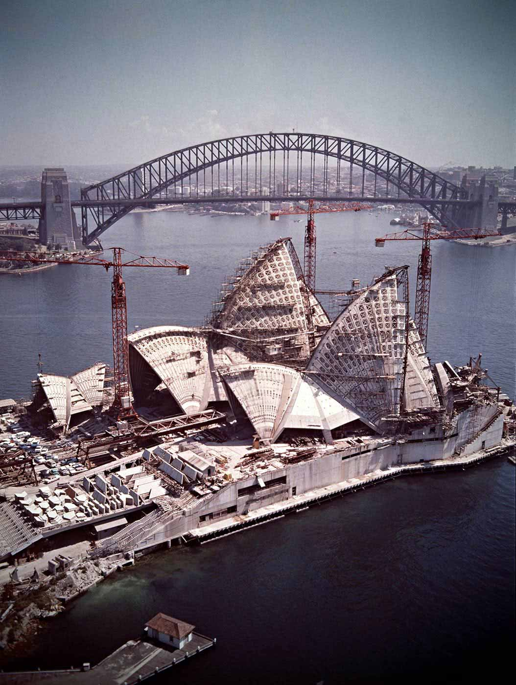 The almost completed Opera House in foreground surrounded by cranes, with Harbour Bridge in background. - click to view larger image