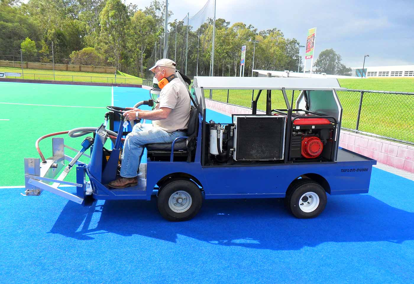 Colour photograph showing a side view of a man sitting on a four-wheeled motorised blue cart. The man steers the cart on a bright blue and green synthetic field surface. - click to view larger image