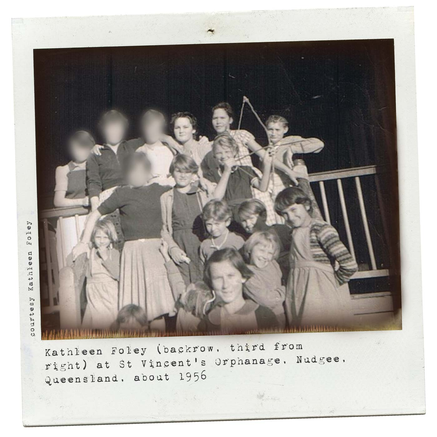 Polaroid photograph showing a group of girls standing at the front of a timber verandah rail. One of the girls holds a small bow and arrow. Some of the older girls' faces have been blurred. Typewritten text at the bottom reads 'Kathleen Foley (back row, third from right) at St Vincent's Orphanage, Nudgee, Queensland, about 1956'. 'Courtesy Kathleen Foley' is typed along the left side.