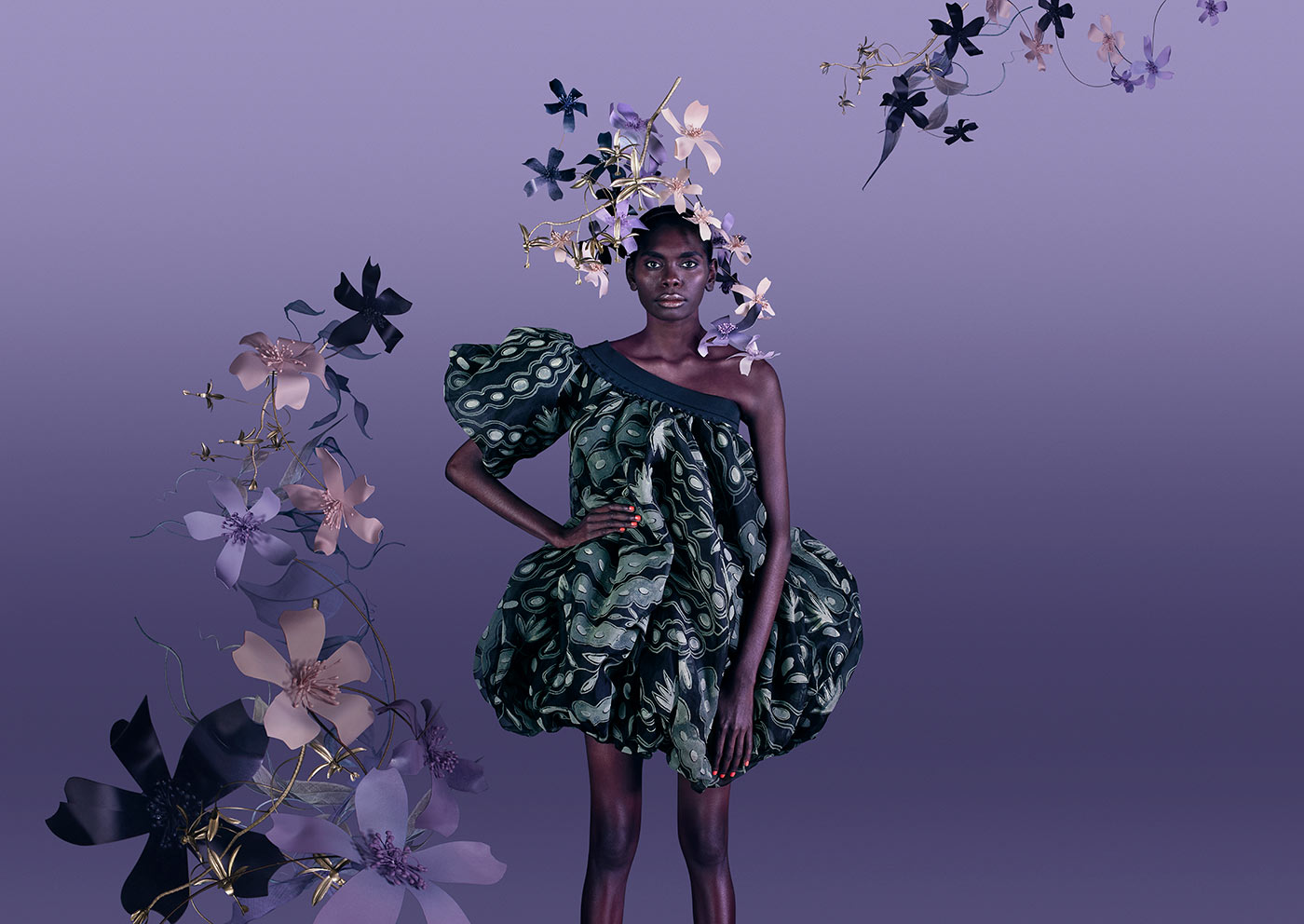Woman standing against a purple backdrop decorated with fabric flowers wearing a short seepod patterned dress with one sleeve and a flower headdress - click to view larger image