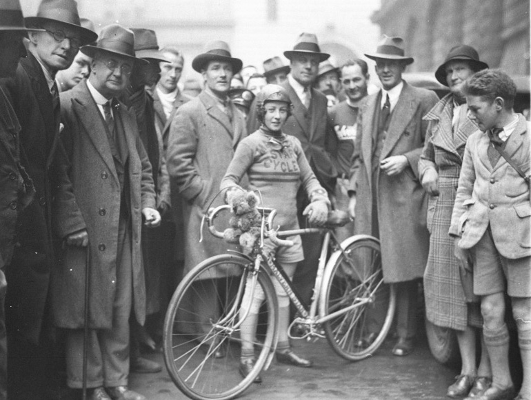 A black and white photo of Billie Samuels with her bike and surrounded by a crowd of people. - click to view larger image