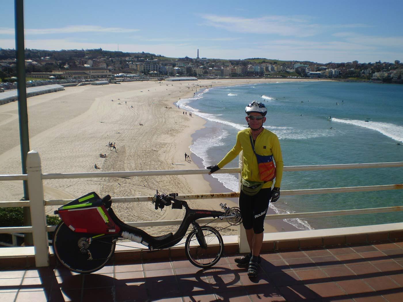 Colour photograph of a cyclist standing beside a recumbent bicycle. Bondi Beach is visible in the background. - click to view larger image