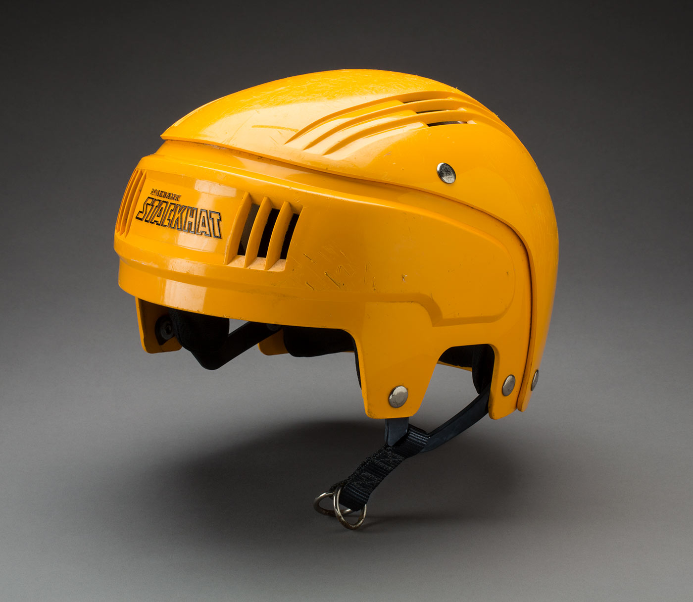 A yellow plastic helmet that has a black nylon chin strap with a metal fastener. The left chin strap is missing.  - click to view larger image