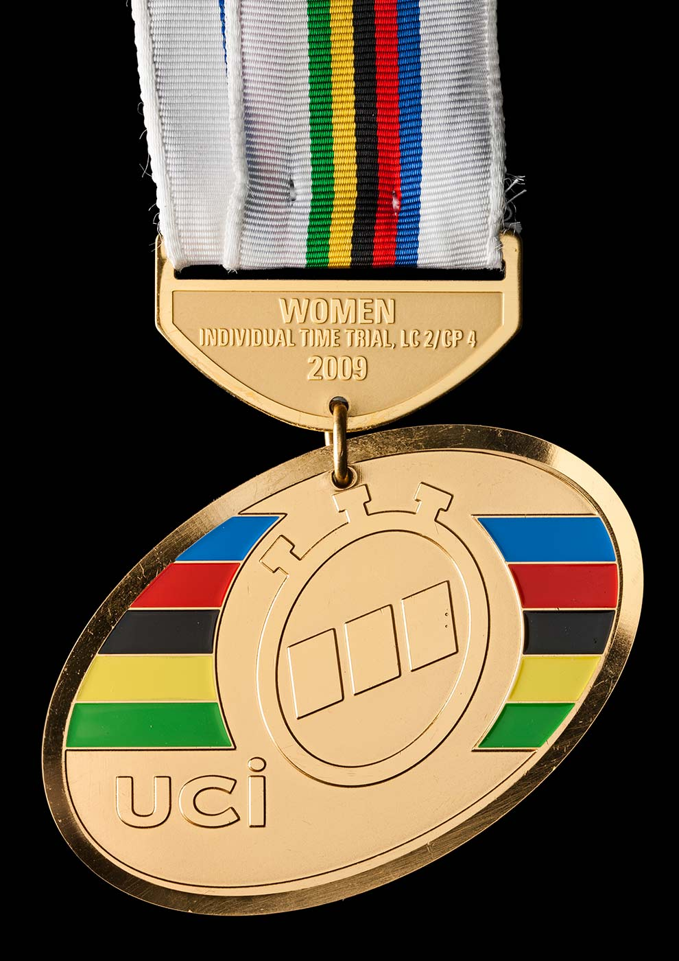 Gold medal hanging from a white ribbon with central multi-coloured stripes. - click to view larger image