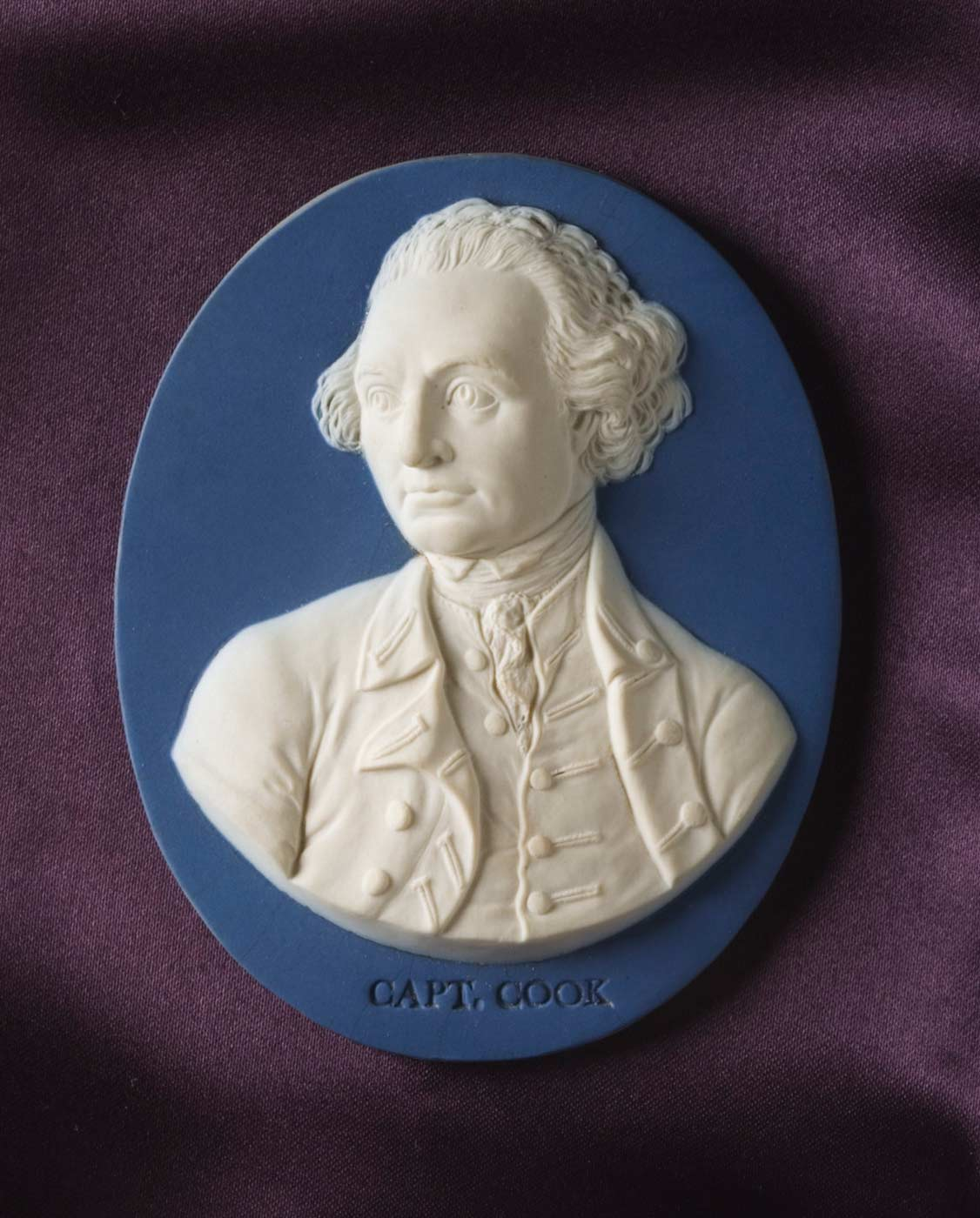 Oval pale blue jasper medallion with a darker blue dip and white jasper portrait of Captain Cook, which has a stamped impression below the portrait which reads 'CAPT. COOK'. - click to view larger image