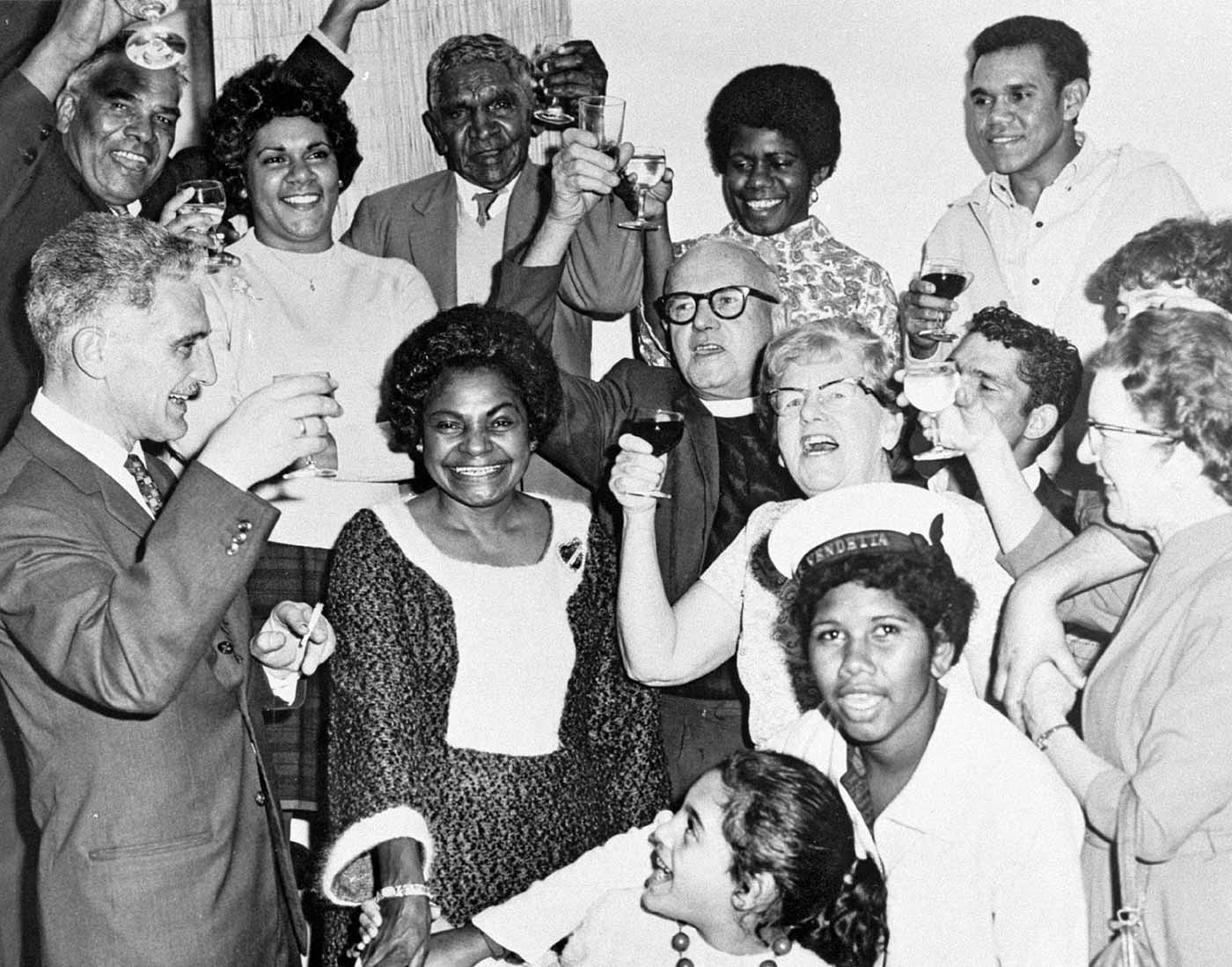 Black and white photo of a group of people cheering and raising their drinks in celebration.