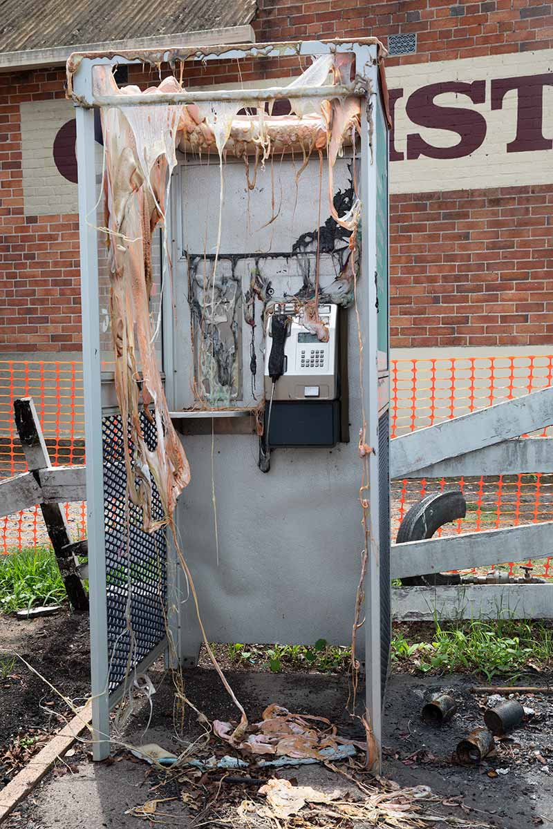 A melted phone booth damaged by fire. - click to view larger image