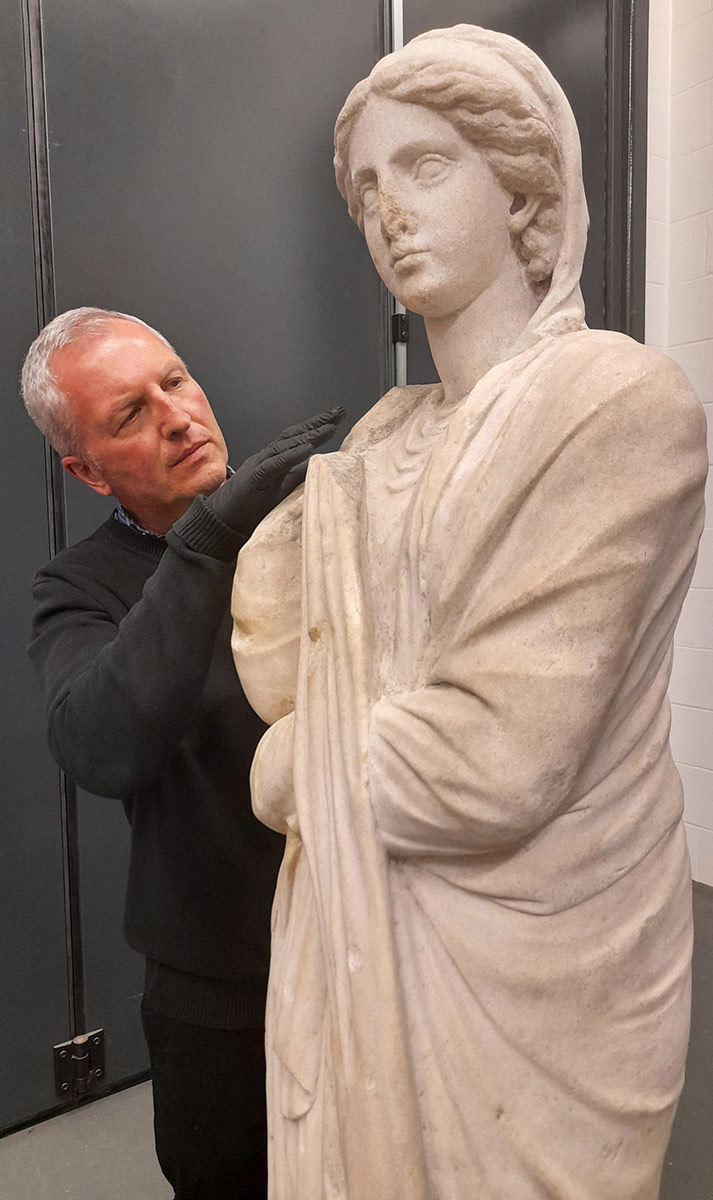 A man with conservation gloves inspects a marble statue of a woman. - click to view larger image