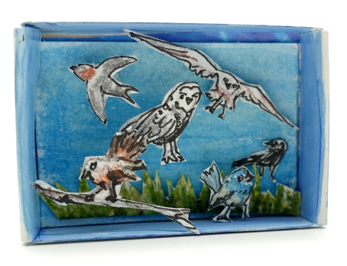 A match-box style container revealing an interior of cut out shapes of birds against a backdrop of foliage. - click to view larger image