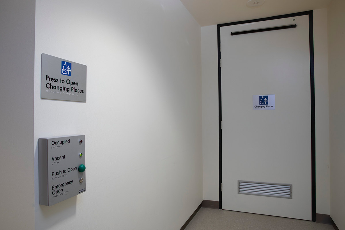 Door with a 'Changing Places' sign and a button operated unit for access on the wall. - click to view larger image