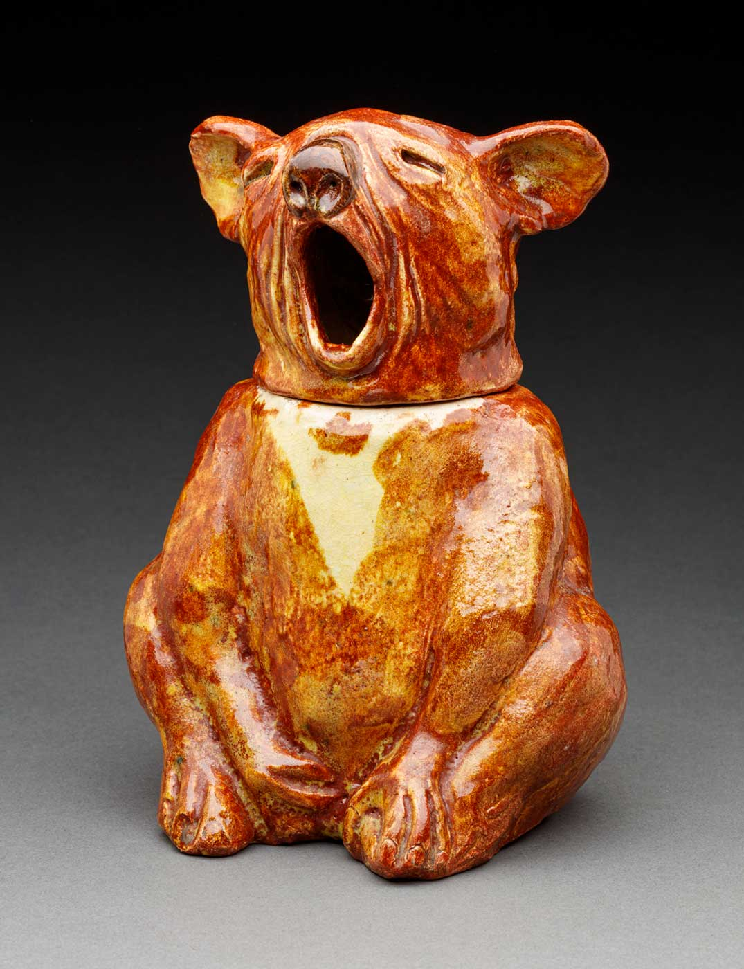A ceramic biscuit jar in the shape of a yawning koala. It is painted in shades of brown and cream.