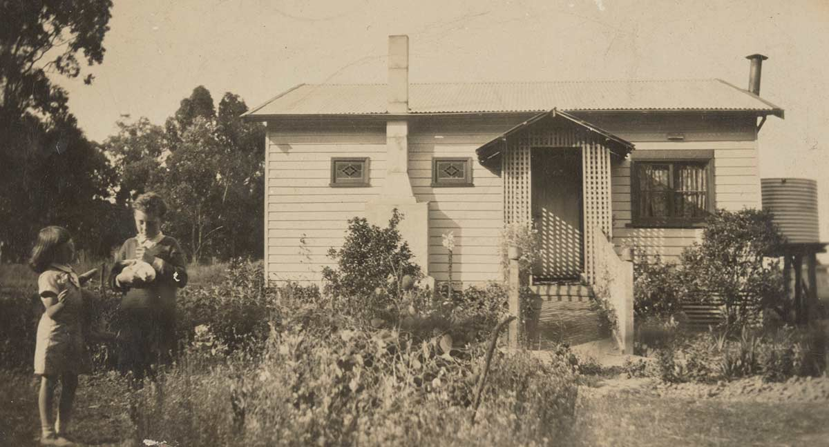 A black and white photograph of a young girl and boy standing in a garden in front of a weatherboard cottage.