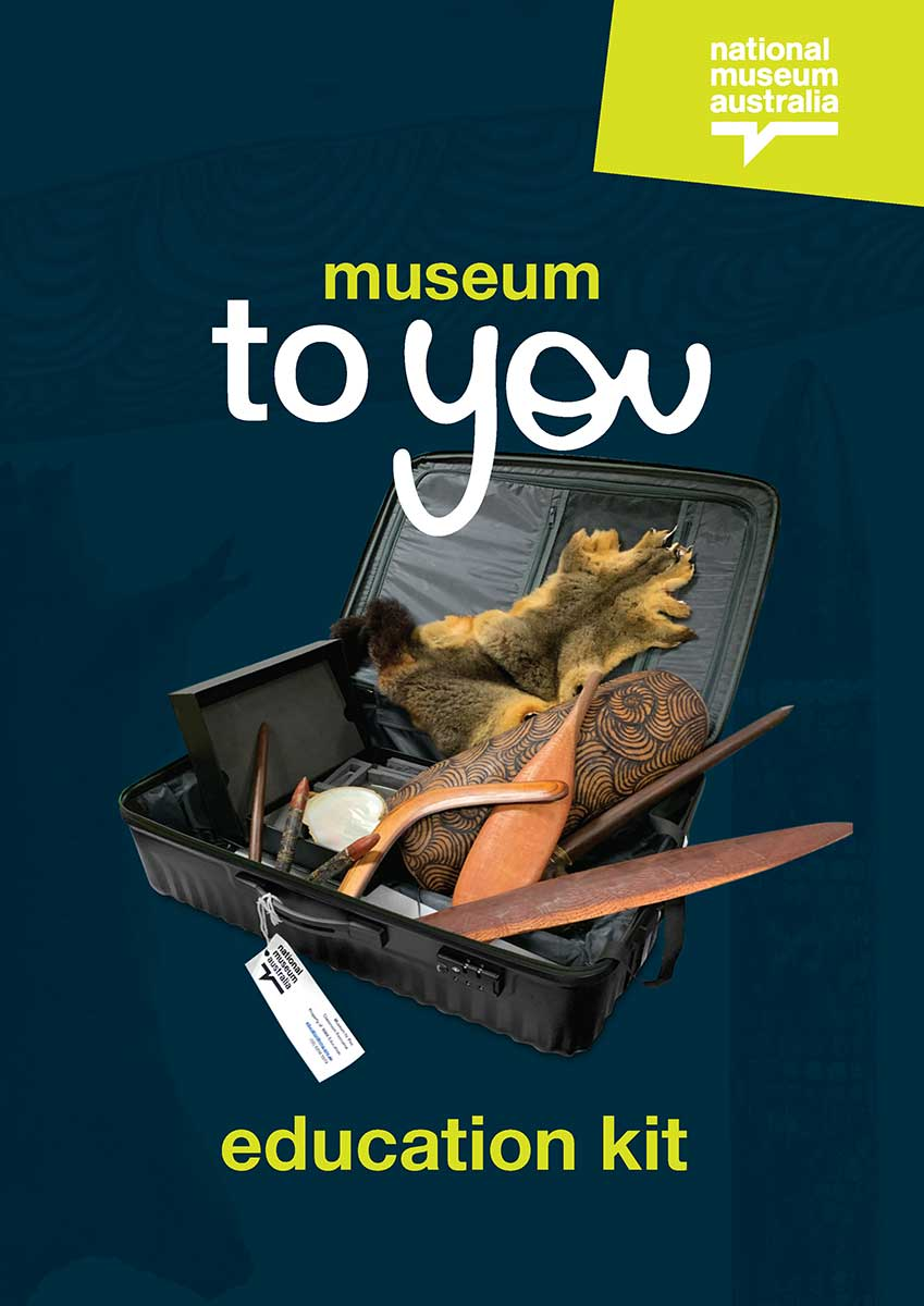 Promotional image of a suitcase with a National Museum of Australia tag containing various objects including clapping sticks, a decorated shield and an animal pelt.
