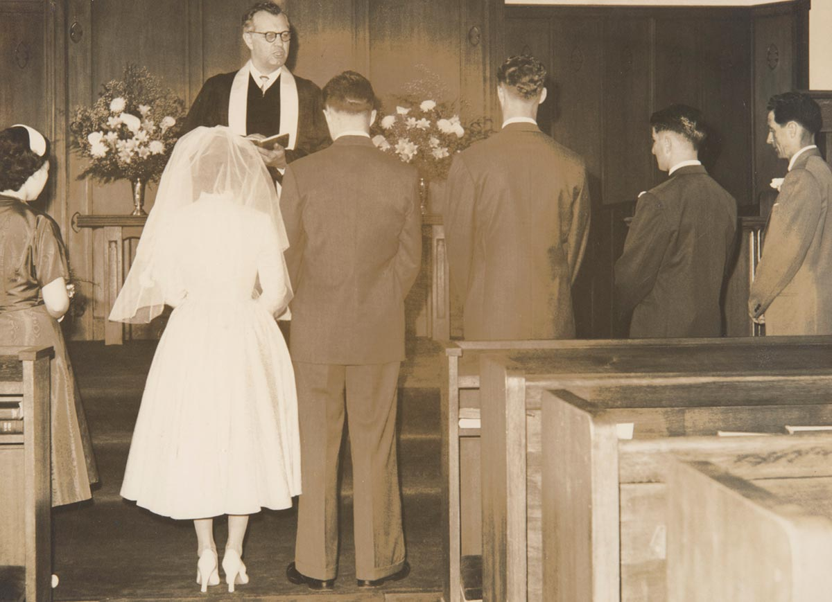 A black and white wedding photograph of seven people in a church, five men and two women. Standing on the left are two women, one of whom is the bride. To the right of her are four men. They are all facing away from the camera, standing in front of a man who appears to be a priest.