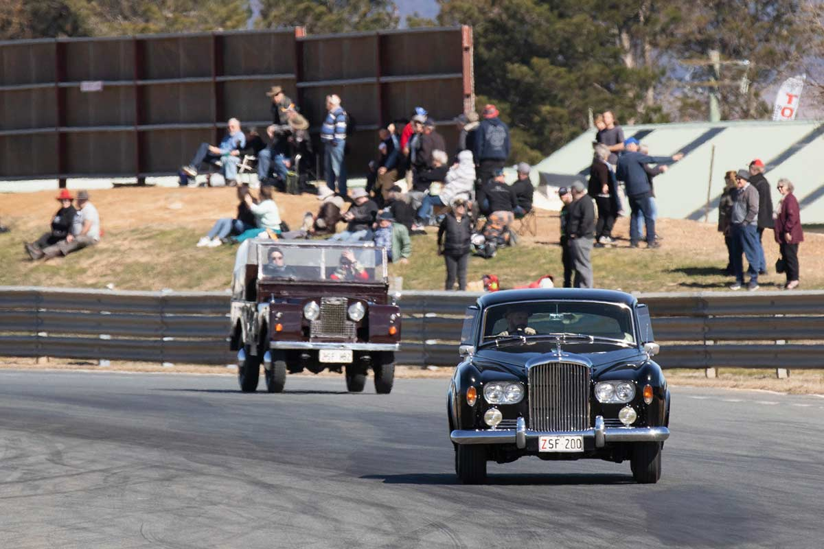 Vintage cars on show at a raceway track with spectators on the side lines. - click to view larger image