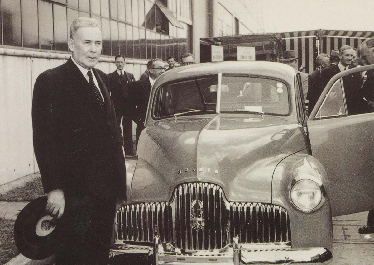 A black and white postcard of Ben Chifley standing in front of a Holden car.  A handwritten inscription is on the back stating