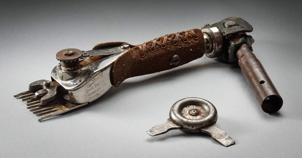 A mechanical shearing handpiece made of metal, with a brown leather hand-grip, a moveable arm at one end, and a detachable metal comb at the other. The handpiece is engraved at the side with 'PRESENTED TO / JACK HOWE / WOLSELEY S.S.M.Co. / January 1893'. The leather hand-grip is laced with a brown leather thong.