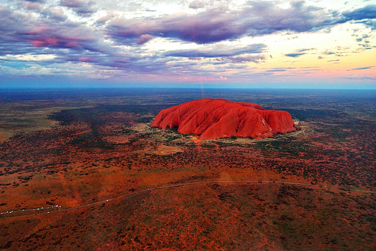 Aerial view of a large orange rock in a desert landscape, with clouds in the evening sky. - click to view larger image