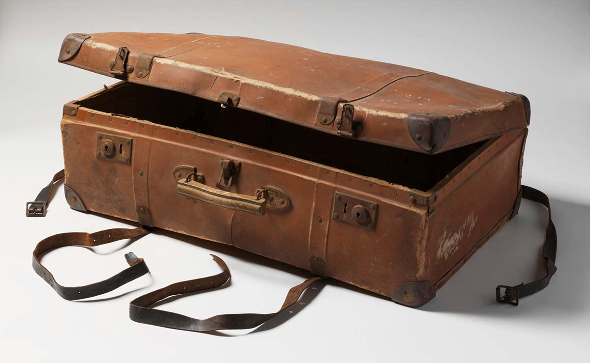 A brown suitcase featuring a wooden handle attached to the top by metal clips, leather corner protectors and metal clasps a a pair of brown and black leather and metal suitcase straps. - click to view larger image