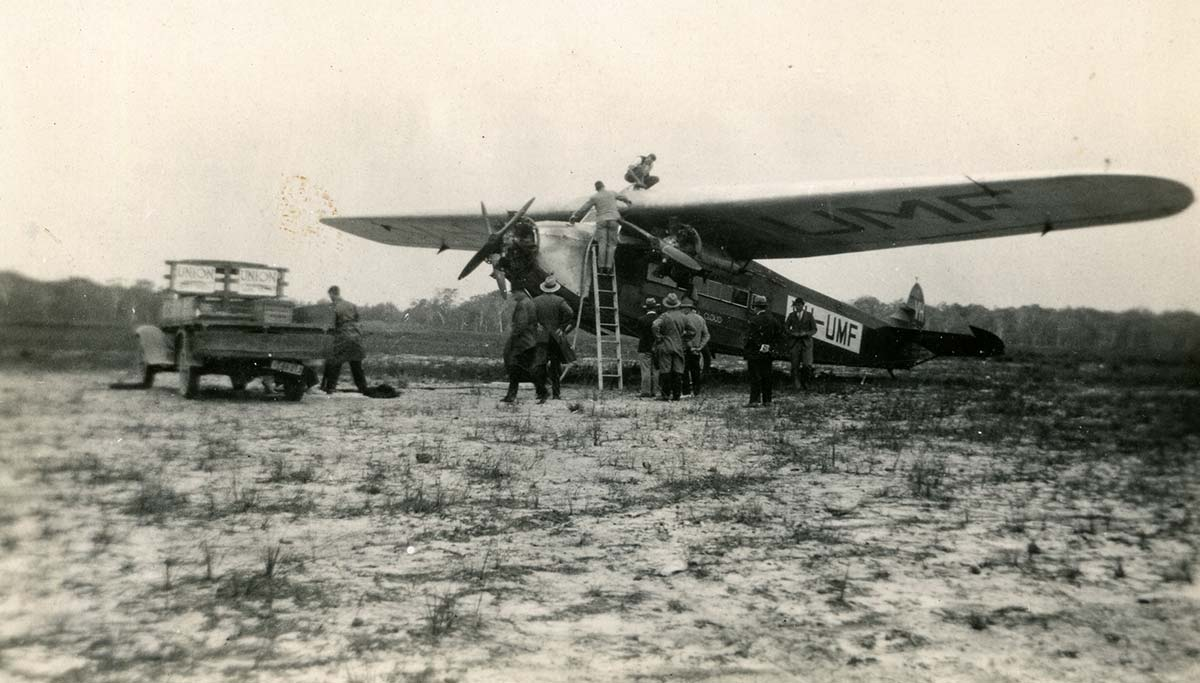Black and white photograph of a small aircraft on the ground. People are gathered around and on top of it.