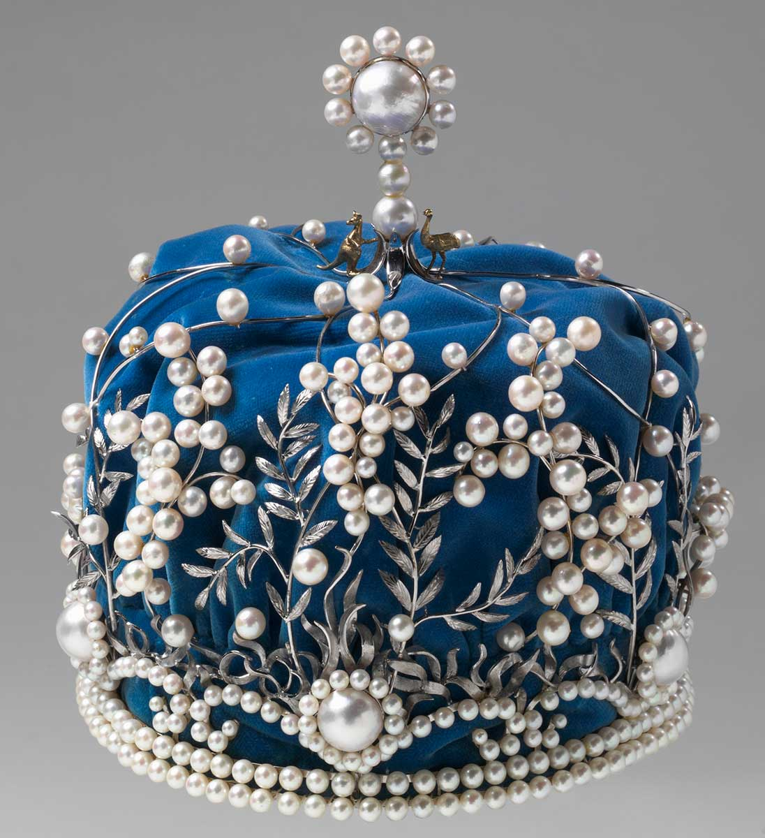 Crown with pearls as wattle flowers and silver leaves, over a blue fabric base. A silver kangaroo and emu stand either side of a larger pearl at the top of the crown. - click to view larger image