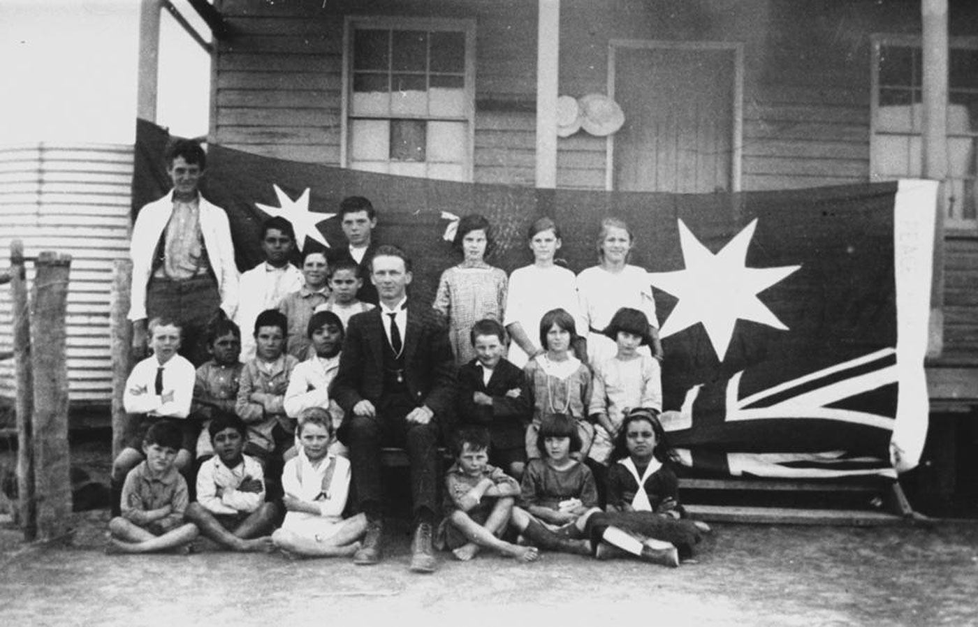 A black and white group photograph of a group of students and a teacher, in three rows, sitting in front of an Australian flag, strung to verandah posts and hanging upside down.  - click to view larger image