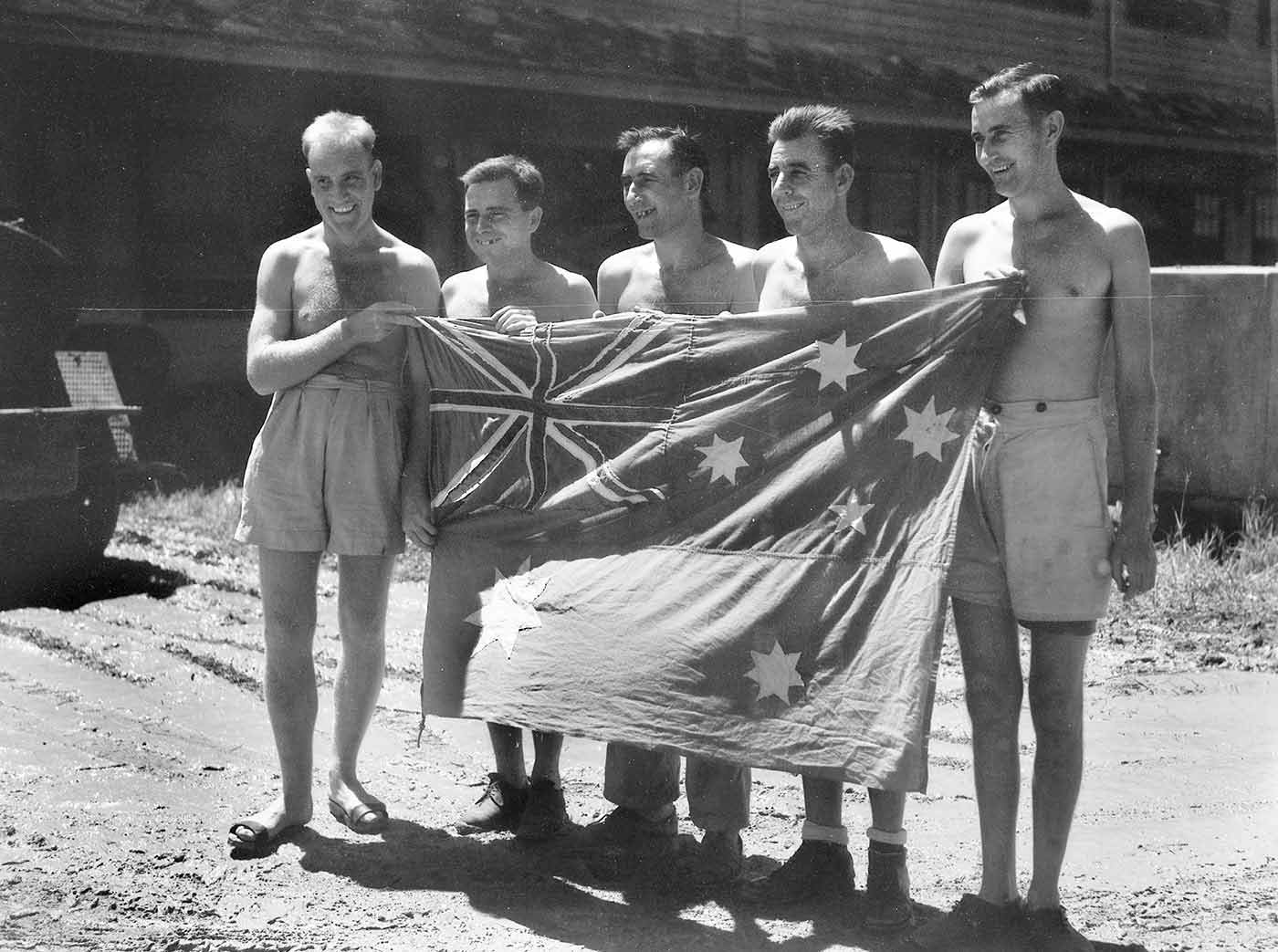 A black and white photograph showing five men standing behind a homemade Australian flag. The men are shirtless.  - click to view larger image