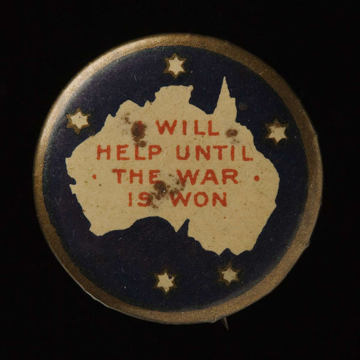 Badge featuring a map of Australia and the Southern Cross. The text on the badge reads 'I WILL HELP UNTIL THE WAR IS WON'. - click to view larger image