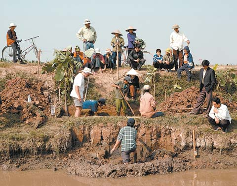 Photo of a team, including Museum conservators, excavating a coffin containing a Vietnamese Bronze Age burial shroud.