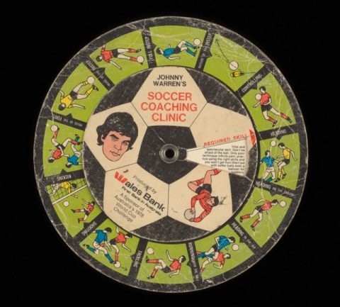 A colour printed cardboard disc with illustrations of football players in different positions, and accompanying descriptive text. There is an illustrated portrait of John Warren at the centre with text 'JOHNNY / WARREN'S SOCCER / COACHING / CLINIC / Produced by / Wales Bank / First Bank in Australia / A Sponsor of / Australia's 1978 / World Cup / Challenge'.