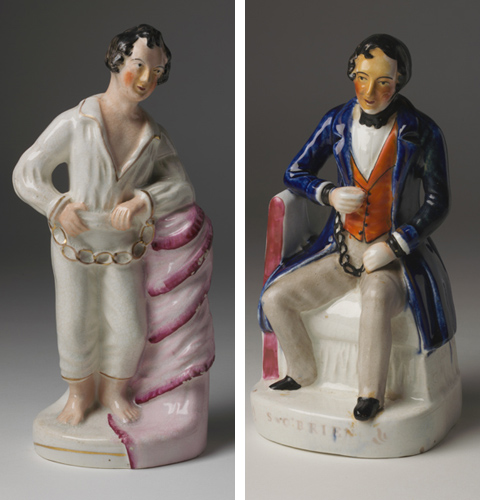 Left: Ceramic figurine depicting a man standing bare foot and leaning against a post draped with pink fabric. The man has short brown hair, is clean shaven and wears an open-necked white shirt and three-quarter length white pants. His wrists are chained with manacles, which are decorated with gold. Right: Ceramic figurine depicting a man sitting on a seat. The man has short brown hair, is clean shaven and wears a blue three-quarter length coat, an orange waistcoat, beige trousers, black shoes and a black cravat. His wrists are chained together with manacles, which are black in colour. The name 'S. O'Brien' is shown on the base of this figurine.