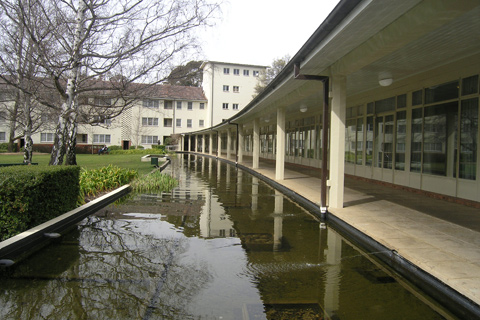 A pond runs the length of a curved verandah, with buildings at the right and rear of the image and gardens at left