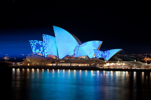 The Sydney Opera House by night, with blue-coloured lights projected onto its sails.