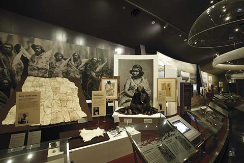 First Australians display featuring the National Museum's Tooloyn Koortakay collection including pastel drawings, lino cuts, possum skin dance ornaments, a selection of tools, and possum skin cloaks.