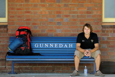 Landscape image showing a man sitting to the far right of a blue, slatted railway bench. 'GUNNEDAH' is painted in white at the centre back of the bench. The man wears a black open-collared T-shirt and khaki shorts and sits with his forearms resting on his thighs. A red and black backpack and a blue sleeping bag sit at the opposite end of the bench. Reddish-coloured bricks form a backdrop.
