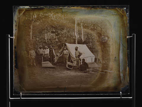 Glass plate showing seven men standing outside a canvas tent, in a bush setting. A child stands to the right of the image, with a woman crouched down beside. Two wooden gold-washing cradles are also visible.