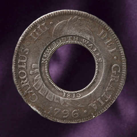 Circular coin with a hole at the centre. 'NEW SOUTH WALES 1813' is stamped around the centre ring. 'CAROLUS IIII DEI GRATIA 1796' is stamped around the outer rim.