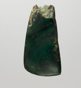 Adze blade made of a light-coloured greenstone (a kind of Jasper or Nephritic stone) with four-edged cross-section and without shoulder neck.