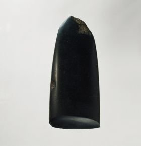 Adze blade made of hard black basalt stone with a rounded off neck, also rounded off lengthwise in cross-section.