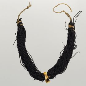Breast ornament with hook. Hung from two black bundles of twisted human hair, connected by a cord. A pendant at the front is made of whale tooth and has the form of a hook.