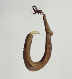 Large fishhook made of brown hardwood with the point made of mother-of-pearl that is secure with plaited coconut fibres.